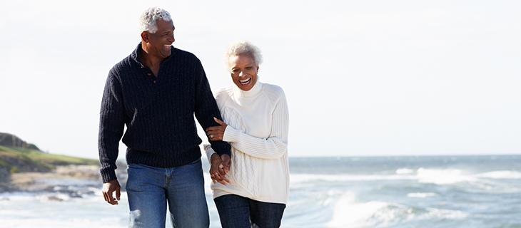 Un vieux couple se tenant la main marchent auprès de l'océan.