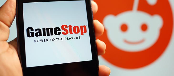Main tenant un appareille mobilière démontrant le Platform GameStop sur l'écran, avec un dessin animé en orange et blanc dans le distance.