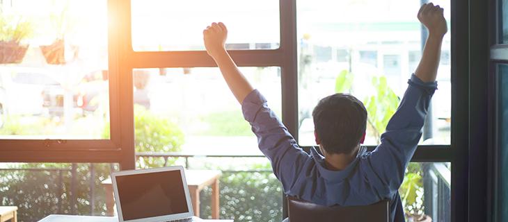Un étudiant s'étirant près de son ordinateur portable.