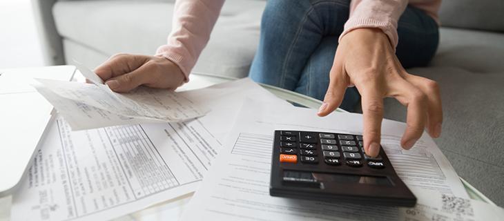Femme qui prépare des documents et utilise une calculatrice.