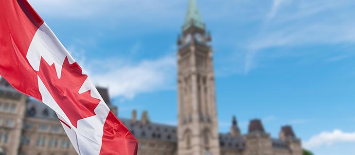 Drapeau du Canada qui flotte au vent avec les édifices du Parlement en arrière-plan