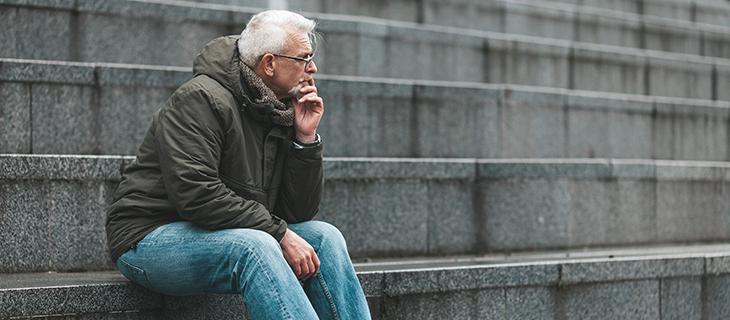 Un homme âgé assit dehors sur des escalier entrain de pensée.