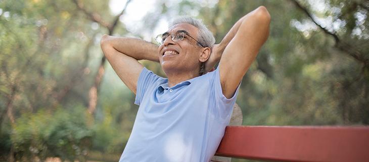 Un homme âgé assis sur un banc dans un parc