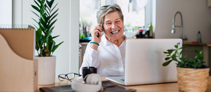 Femme âgée travaillant à domicile sur un ordinateur portable et utilisant un téléphone intelligent.