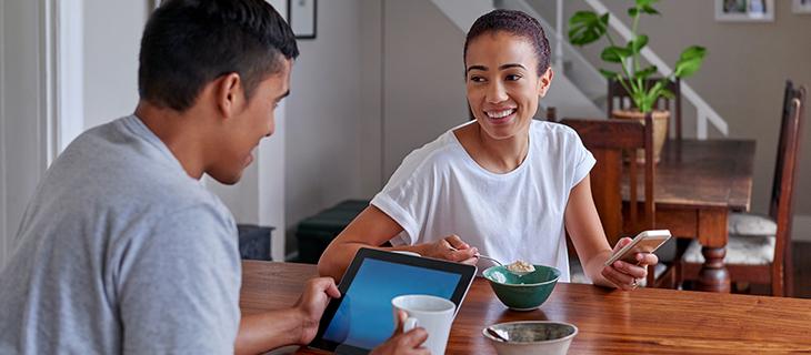 Couple qui déjeune en regardant une tablette et un téléphone