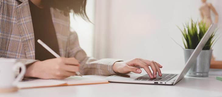Jeune femme d'affaires tapant sur un ordinateur portable et écrivant dans un carnet de notes