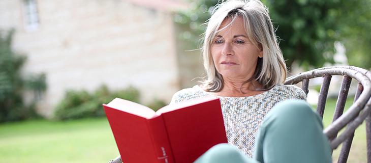 Femme mature relaxant sur une chaise en lisant un livre