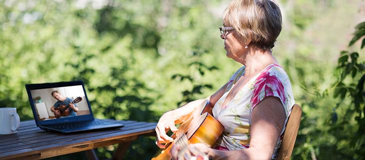 Portrait d'une femme âgée qui joue de la guitare dans sa cour en regardant son ordinateur pour suivre son cours en ligne