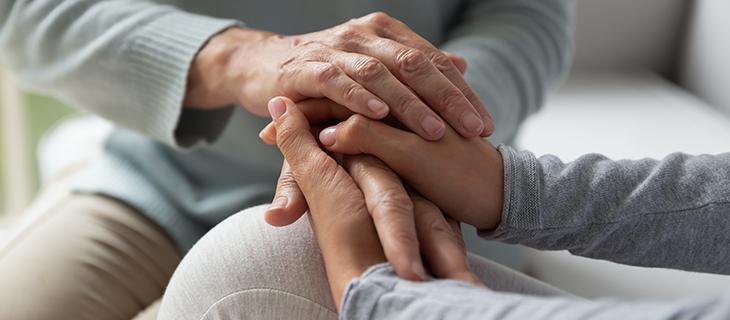 Portrait d'une mère âgée et de sa fille adulte qui se tiennent les mains