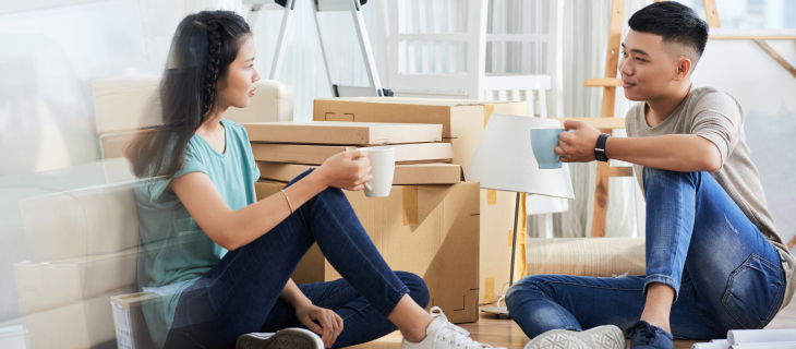 Etudiant assit sur le plancher tenant une tasse de café, entouré de boîtes de déménagement.