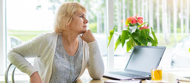 Femme d'âge moyen assise à une table près de la fenêtre dans sa maison et travaillant sur un portable