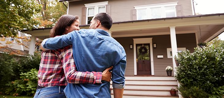 Vue arrière d'un jeune couple marchant vers leur nouvelle maison