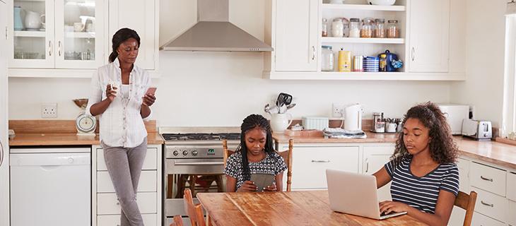Une mère regarde son téléphone cellulaire pendant que ses deux filles travaillent à l'ordinateur à la table de la cuisine