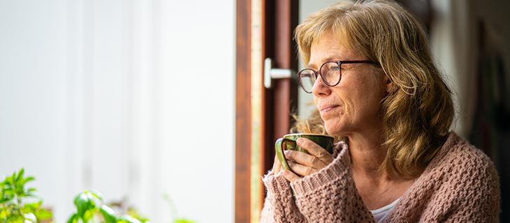 Femme âgée dégustant un café tout en regardant par la fenêtre