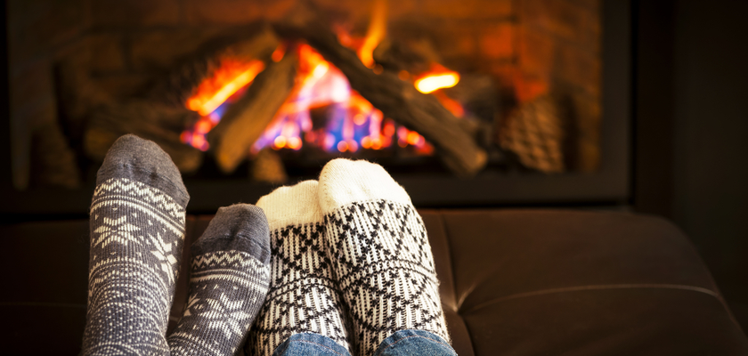 two people in socks by a fireplace