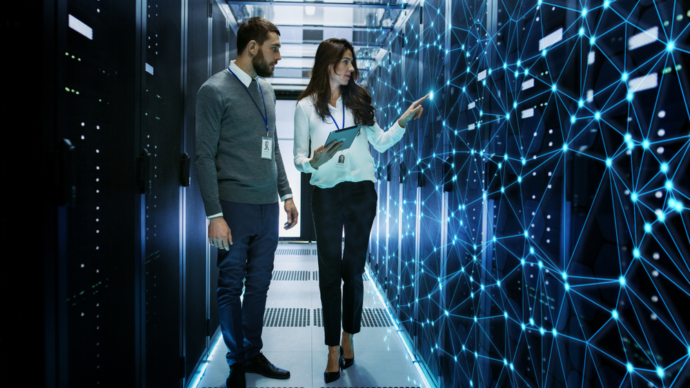 Two IT managers working in data center with overlay of an integrated network web.