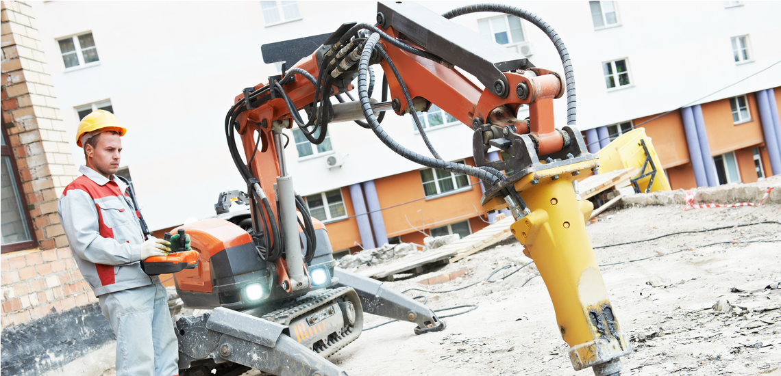 construction worker uses controller for robotic arm on jobsite