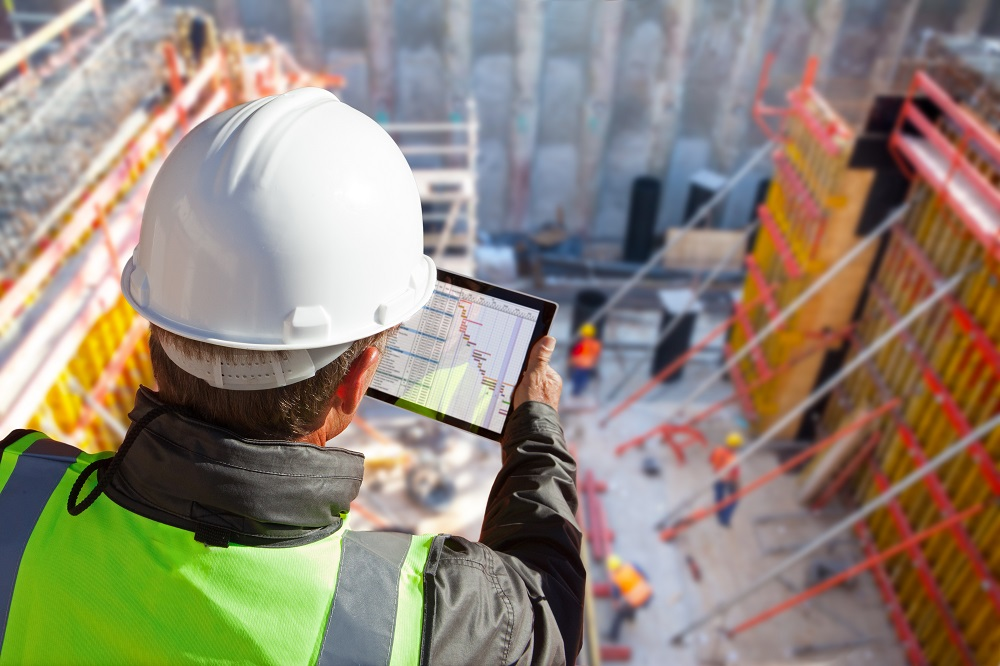 Site superintendent reviews schedules on tablet on a construction job site