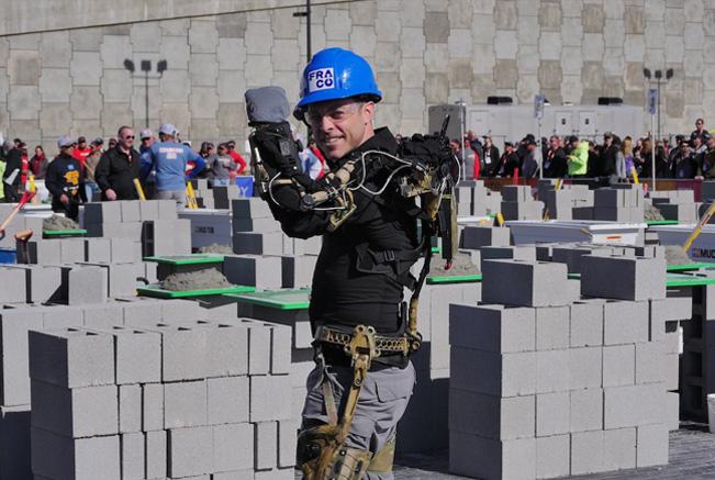 construction worker uses fraco exoskeleton by mawashi to lift concrete cinderblocks