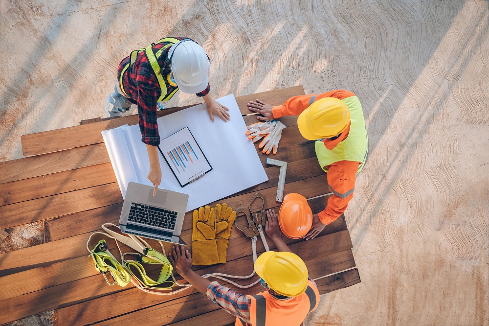 construction workers on jobsite look at laptop and paper drawings