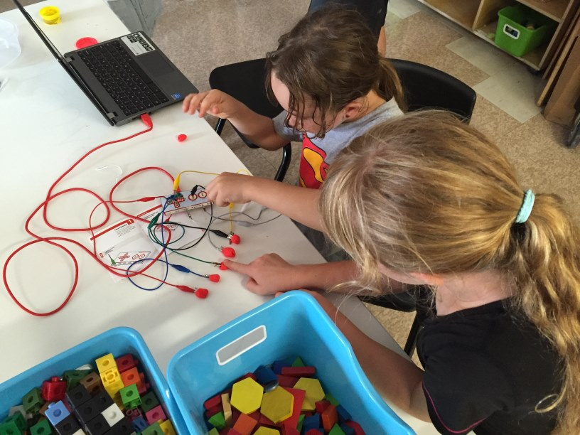 Two children operate a MaKey MaKey device