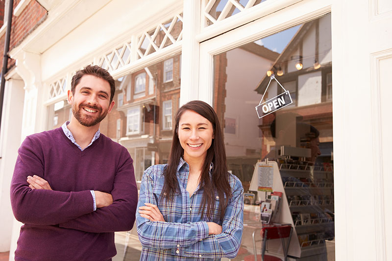 A woman and a man standing in front of a brick and mortar retail location