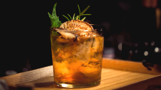 Craft cocktail with rosemary, mint, and bourbon