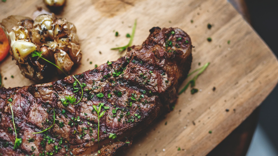 Gourmet grilled steak and oven roasted garlic with fresh herb garnish
