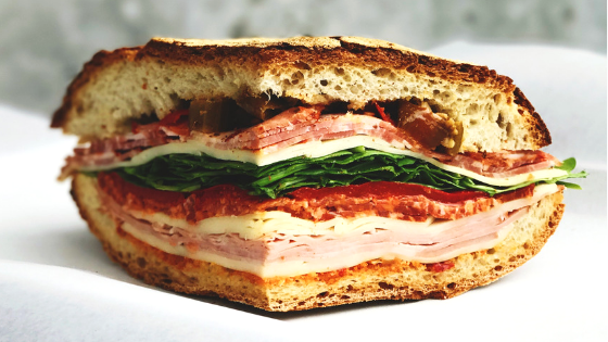 Cold cuts, lettuce, tomatoes, and garnishes on thick artisan bread