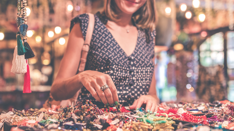 A bohemian woman shopping for jewelry at a bazaar to try a different customer experience