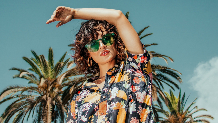 Female model wearing sunglasses in a tropical setting to represent the high fashion customer experience
