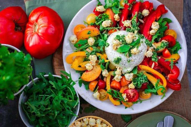 Tomatoes, colorful vegetables, and a salad with yogurt topping to represent a successful grocery store customer experience