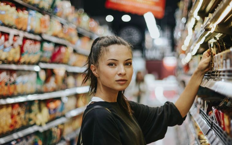 A young woman wearing black shopping in a gourmet supermarket aisle getting the full in-store customer experience