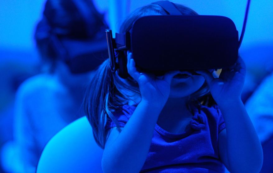 A little girl and her father wearing VR goggles to see a new customer experience
