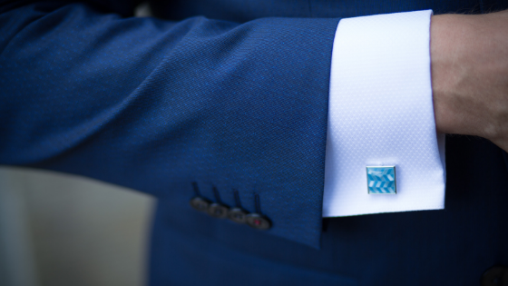 A dark blue suit and view of a man's turquoise blue cufflink and Brooks Brothers quality