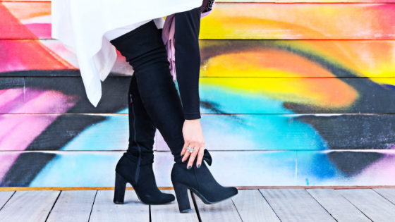 A colorful graffiti mural and a woman wearing black high fashion boots evoking style of iconic retailers