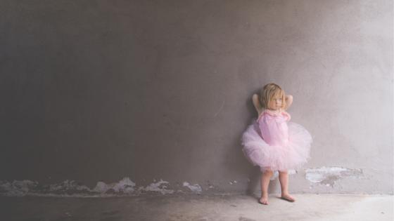 Little blonde girl wearing a pink ballet leotard and a pink tutu