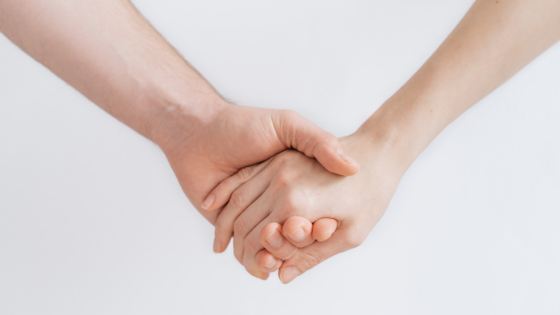 A man and a woman holding hands against a white background symbolic of the relationship between brands and customers