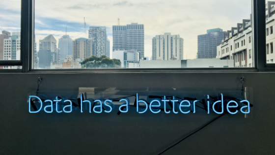 Data has a better idea in blue neon letters on an office wall with below a window with a city skyline
