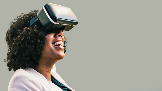 Black woman wearing VR goggles with a smile on her face