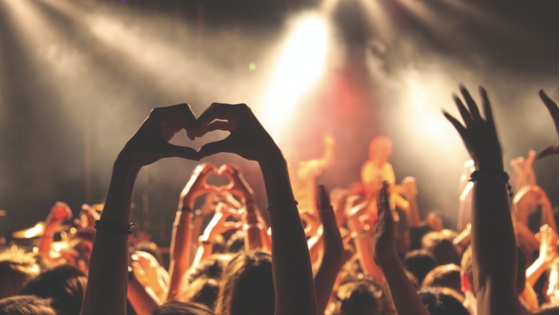 Fans at a concert making heart symbols with their hands