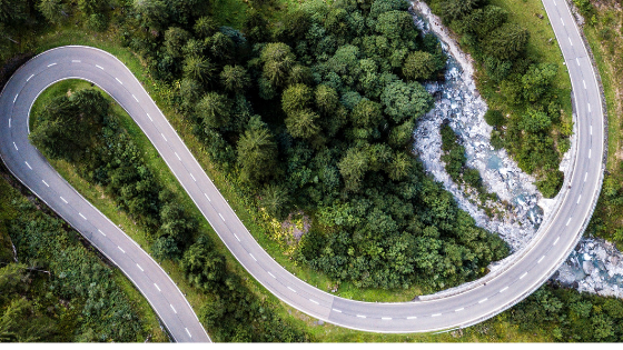 A winding paved road surrounded by trees and greenery symbolic of a customer journey