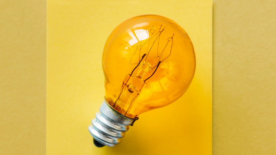 A yellow light bulb against a yellow background symbolic of data insights in customer journey mapping