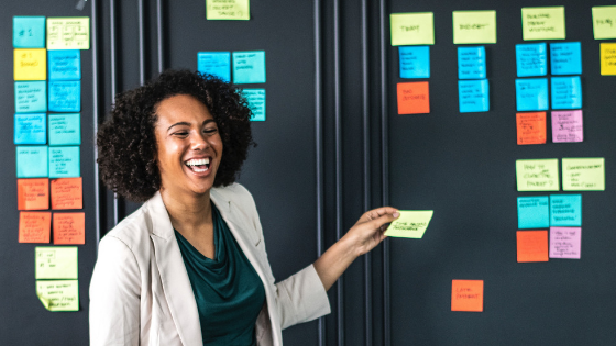 Woman smiling and using colorful Post-It notes to explain the value of CRM projects