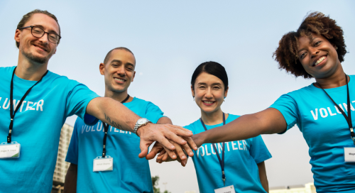 A group of people wearing blue t-shirts with the word volunteer