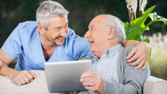 Middle aged man in pale blue scrubs holding a tablet and caring for an elderly man