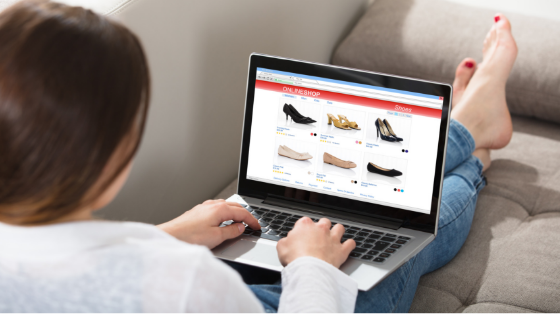 Women seamlessly shopping for shoes on a laptop top while sitting on a couch