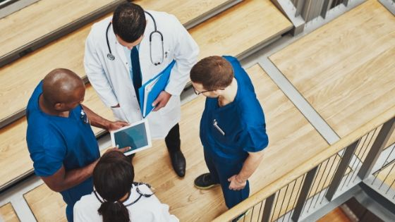 Hospital staff standing in a circle looking at healthcare data on a tablet