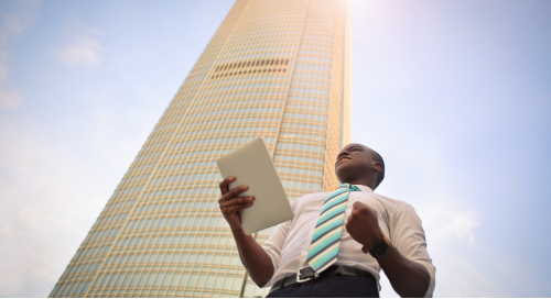 An African American businessman reading a CRM report standing in front of a building on a sunny day