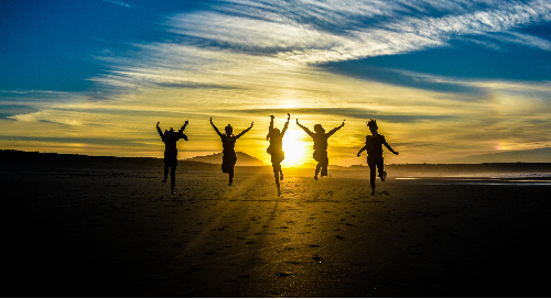 People jumping and celebrating with their silhouettes against a sunset